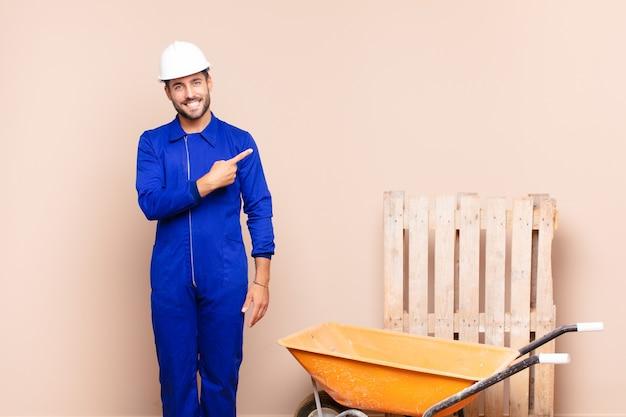 Jonge man die vrolijk glimlacht, zich gelukkig voelt en naar de zijkant en naar boven wijst, voorwerp in het bouwconcept van de exemplaarruimte toont
