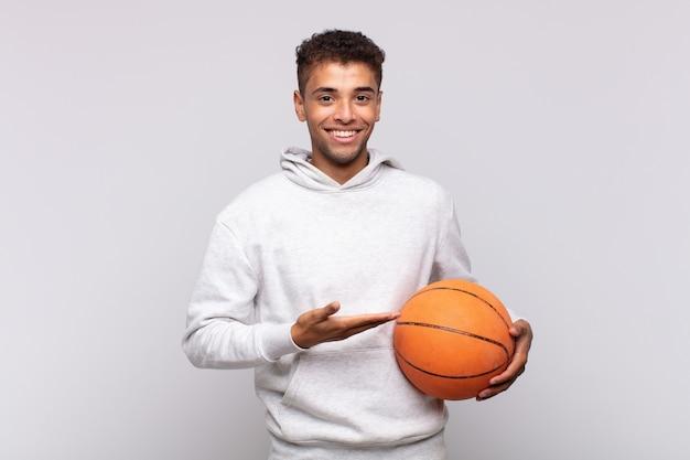 Jonge man die vrolijk lacht, zich gelukkig voelt en een concept in kopieerruimte toont met de palm van de hand. mand concept