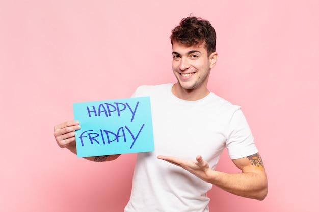 Jonge man die vrolijk lacht, zich gelukkig voelt en een concept in kopieerruimte toont met de palm van de hand
