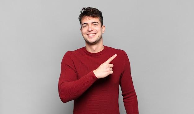 Jonge man die vrolijk lacht, zich gelukkig voelt en naar de zijkant en naar boven wijst, een object in de kopieerruimte laat zien