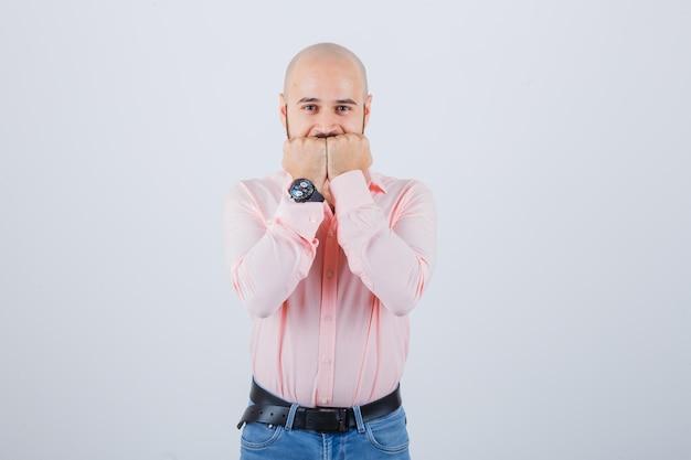 Jonge man die vuisten op de mond houdt in een roze shirt, spijkerbroek en er gelukkig uitziet, vooraanzicht.