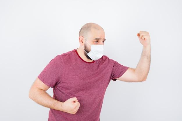 Jonge man die vuisten opheft in roze t-shirt, masker en er agressief uitziet. vooraanzicht.
