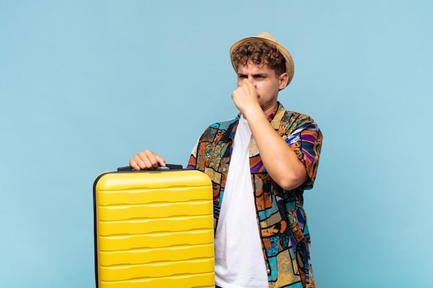 Jonge man die walgt, neus vasthoudt om te voorkomen dat hij een vieze en onaangename stank ruikt. vakantie concept