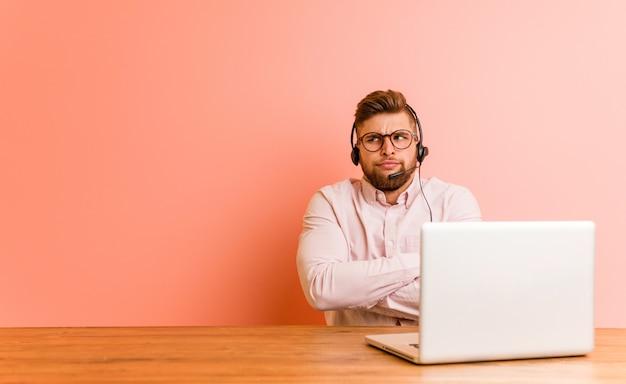 Jonge man die werkt in een callcenter fronsen gezicht in ongenoegen, houdt armen gevouwen