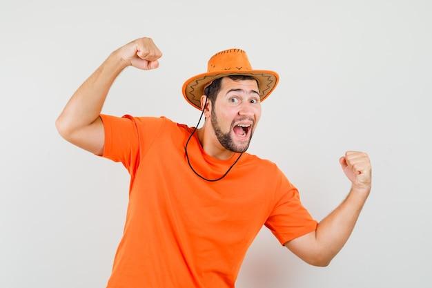 Jonge man die winnaargebaar in oranje t-shirt, hoed toont en er zalig uitziet. vooraanzicht.