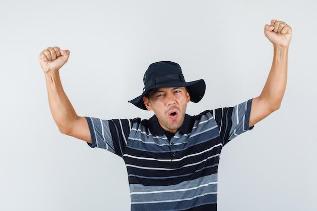 Jonge man die winnaargebaar in t-shirt, hoed toont en er gelukkig uitziet. vooraanzicht.
