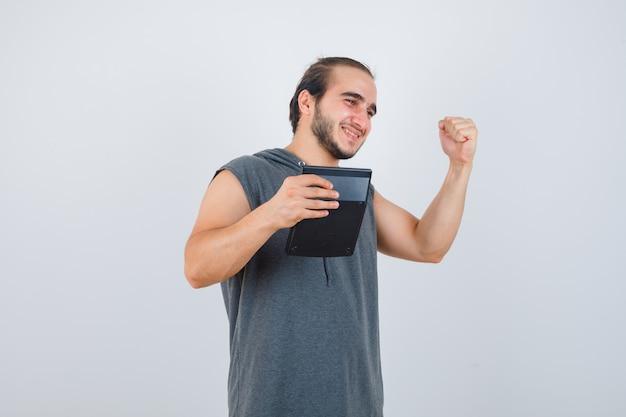 Jonge man die winnaargebaar toont, zijwaarts in hoodie staat en er knap uitziet.