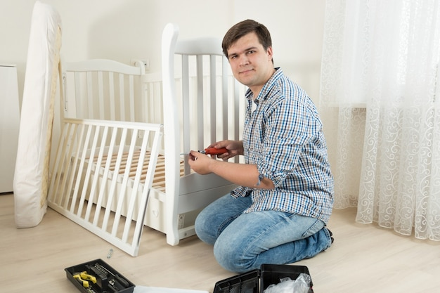 Jonge man die wit houten bed in de kinderkamer monteert voor aanstaande baby