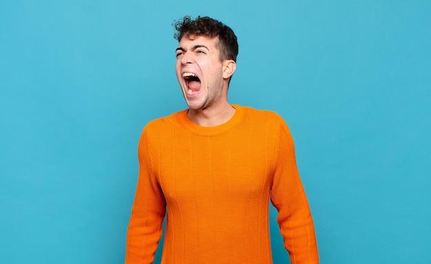 Jonge man die woedend schreeuwt, agressief schreeuwt, er gestrest en boos uitziet