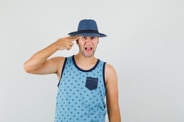 Jonge man die zelfmoordgebaar maakt in blauwe hemd, hoed en nerveus kijkt