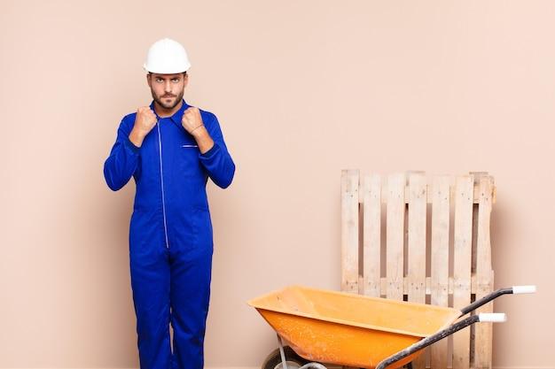 Jonge man die zelfverzekerd, boos, sterk en agressief kijkt, met vuisten klaar om te vechten in het bouwconcept van de bokspositie