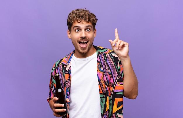 Jonge man die zich als een blij en opgewonden genie voelt na het realiseren van een idee, opgewekt de vinger opstekend, eureka !. vakantie concept