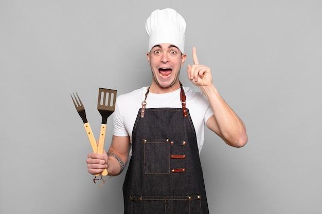 Jonge man die zich als een blij en opgewonden genie voelt na het realiseren van een idee, opgewekt de vinger opstekend, eureka!