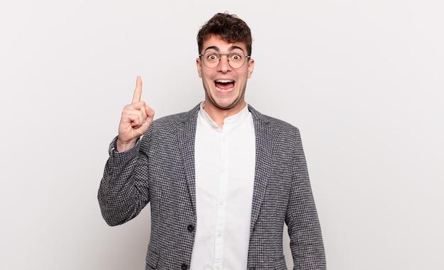 Jonge man die zich als een gelukkig en opgewonden genie voelt na het realiseren van een idee, opgewekt de vinger opstekend, eureka!