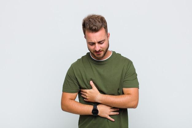 Jonge man die zich angstig, ziek, ziek en ongelukkig voelt, pijnlijke buikpijn of griep heeft