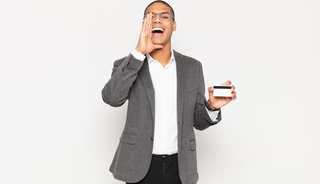 Jonge man die zich blij, opgewonden en positief voelt en een grote schreeuw geeft met de handen naast de mond