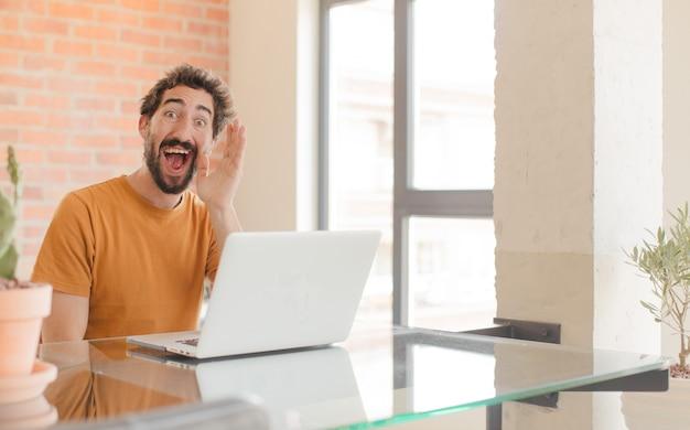 Jonge man die zich blij opgewonden en positief voelt en een grote schreeuw geeft met de handen naast de mond