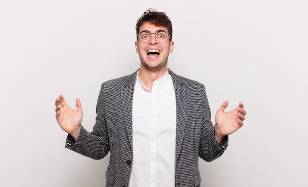 Jonge man die zich blij, opgewonden, verrast of geschokt voelt, lacht en verbaasd is over iets ongelooflijks