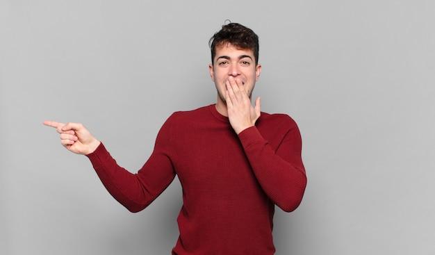 Jonge man die zich gelukkig, geschokt en verrast voelt, de mond bedekt met de hand en naar de laterale kopie ruimte wijst