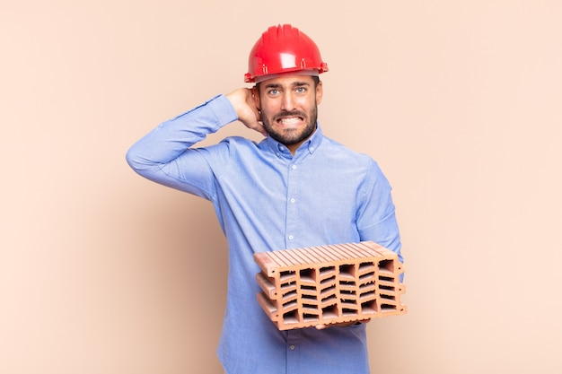 Jonge man die zich gestrest, bezorgd, angstig of bang voelt, met de handen op het hoofd, in paniek raakt bij vergissing. architect concept