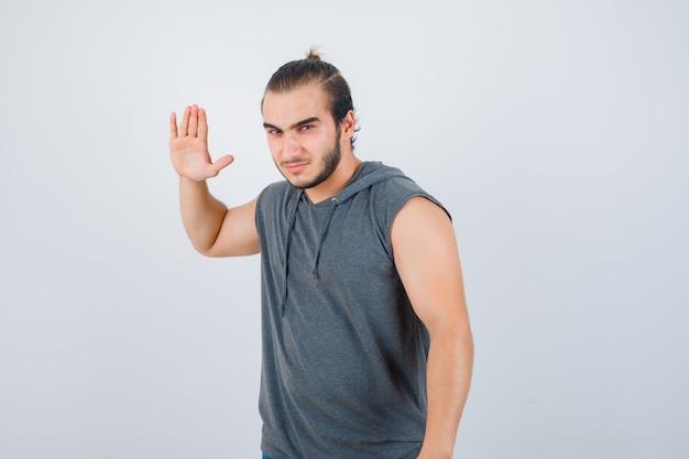 Jonge man die zich klaarmaakt om iemand in mouwloze hoodie te slaan en boos kijkt. vooraanzicht.