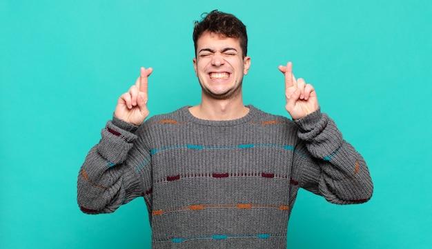 Jonge man die zich nerveus en hoopvol voelt, vingers kruist, bidt en hoopt op geluk
