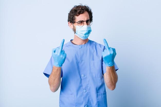Jonge man die zich provocerend, agressief en obsceen voelt, de middelvinger omdraait, met een rebelse houding. coronavirus concept