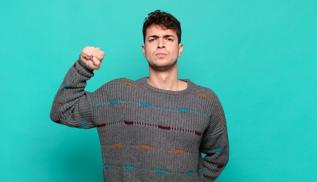 Jonge man die zich serieus, sterk en rebels voelt, vuist opstekend, protesteert of vecht voor revolutie