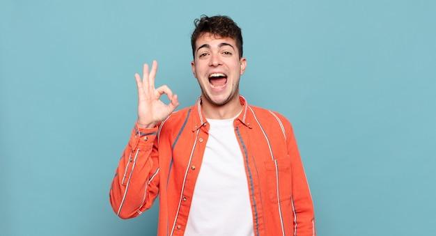 Jonge man die zich succesvol en tevreden voelt, glimlachend met wijd open mond, goed teken makend met de hand