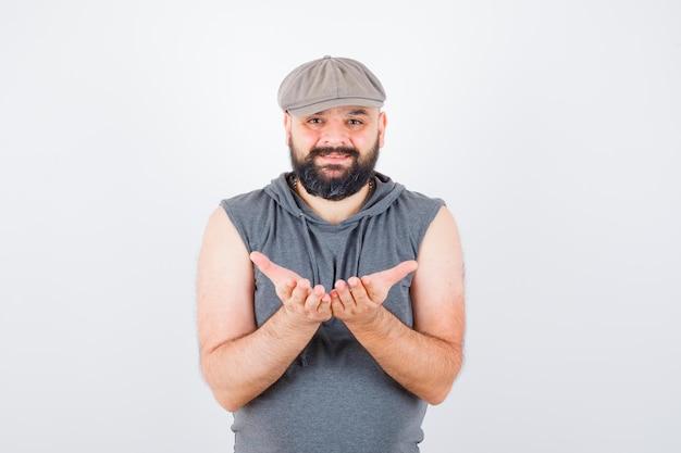 Jonge man die zich tot een kom gevormde handen uitstrekt in mouwloze hoodie, pet en er gelukkig uitziet, vooraanzicht.
