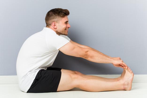 Jonge man die zich uitstrekt beoefenen van yoga