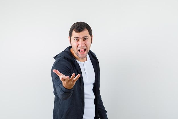 Jonge man die zich uitstrekt hand in vragend gebaar in t-shirt, jasje en op zoek boos. vooraanzicht.
