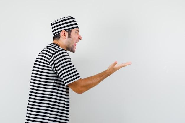Jonge man die zich uitstrekt hand op agressieve manier in t-shirt, hoed.