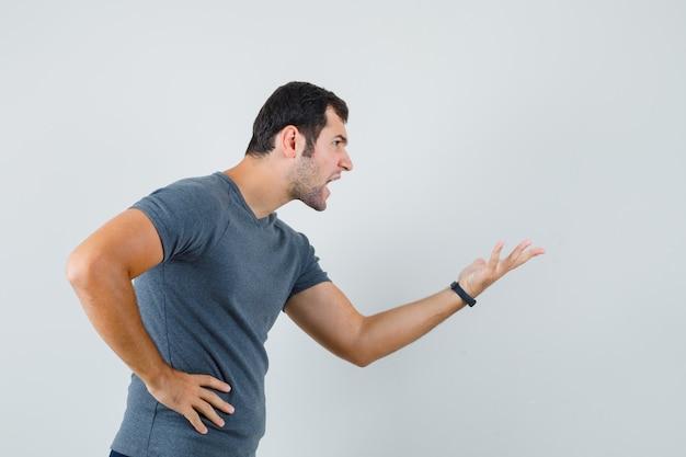 Jonge man die zich uitstrekt hand op vragende manier in grijs t-shirt en boos kijkt