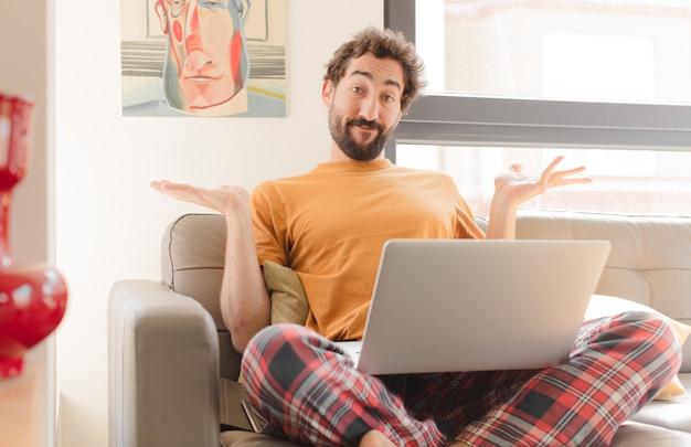 Jonge man die zich verbaasd en verward voelt, twijfelt aan het wegen of verschillende opties kiest met een grappige uitdrukking