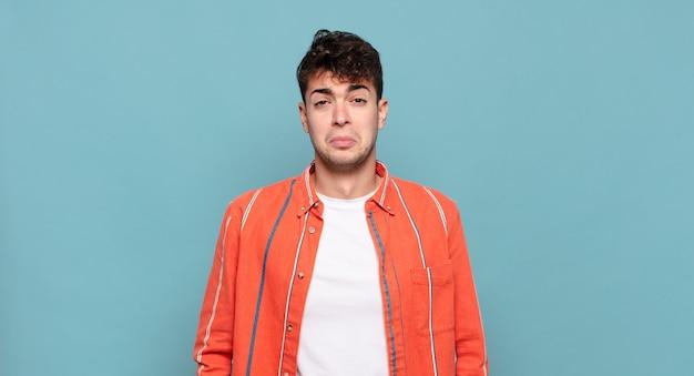 Jonge man die zich verdrietig en zeurderig voelt met een ongelukkige blik, huilen met een negatieve en gefrustreerde houding