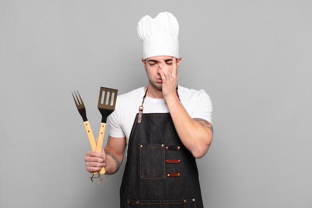 Jonge man die zich verveeld, gefrustreerd en slaperig voelt na een vermoeiende, saaie en vervelende taak, gezicht met hand vasthoudend
