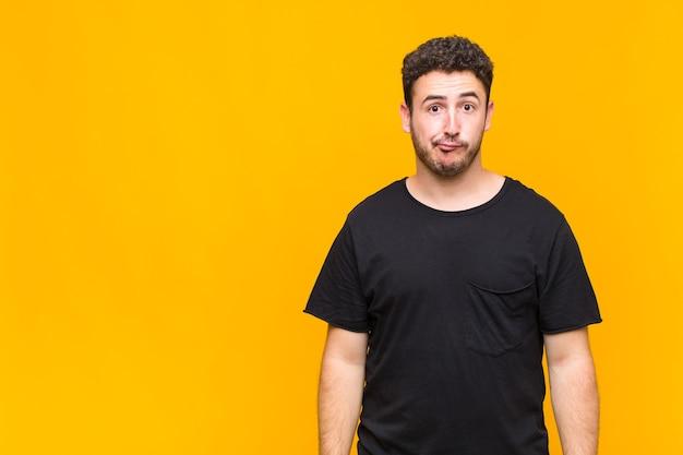 Jonge man die zich verward en twijfelachtig voelt, zich afvraagt of probeert te kiezen of een beslissing te nemen