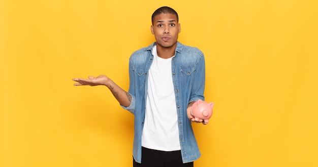 Jonge man die zich verward en verward voelt, twijfelt, weegt of verschillende opties kiest met grappige uitdrukking