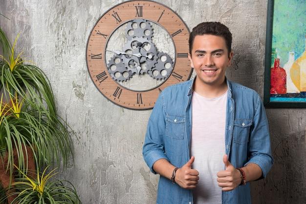 Jonge man die zich voordeed op marmeren achtergrond. hoge kwaliteit foto