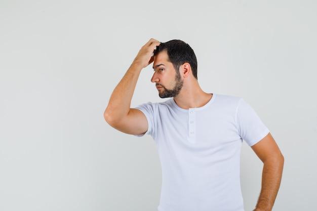 Jonge man die zich voordeed terwijl hij hand op zijn voorhoofd in t-shirt houdt en er cool uitziet. vooraanzicht.