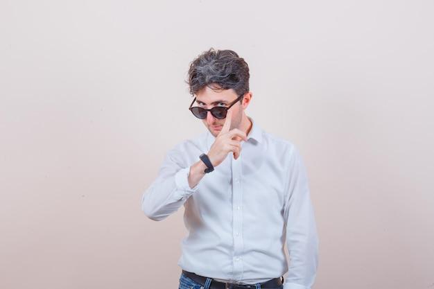 Jonge man die zich voordeed terwijl hij over een bril kijkt in een wit overhemd, een spijkerbroek en er elegant uitziet