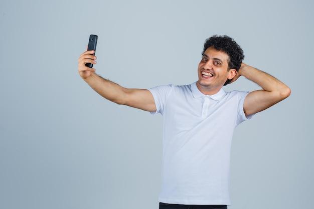 Jonge man die zich voordeed terwijl hij selfie in wit t-shirt nam en er gelukkig uitzag. vooraanzicht.