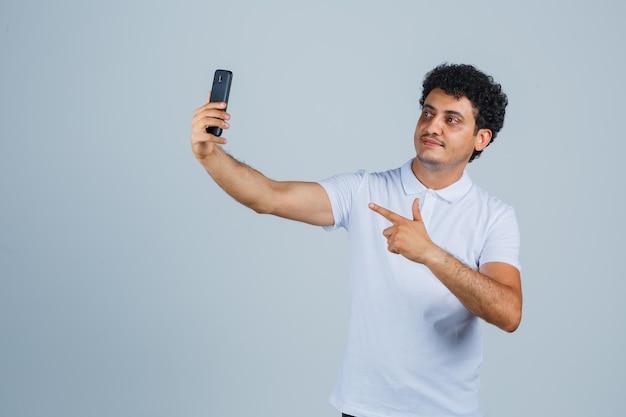 Jonge man die zich voordeed terwijl hij selfie in wit t-shirt nam en er schattig uitzag. vooraanzicht.