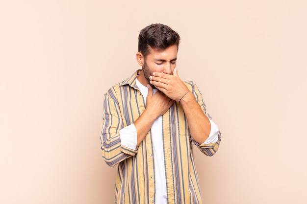 Jonge man die zich ziek voelt met een zere keel en griepsymptomen, hoest met bedekte mond