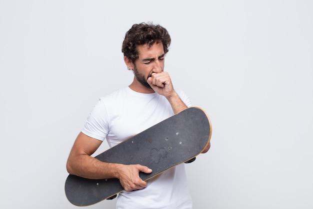 Jonge man die zich ziek voelt met keelpijn en griepsymptomen, hoesten met bedekte mond