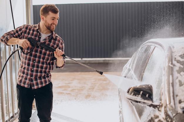 Jonge man die zijn auto wast bij carwash