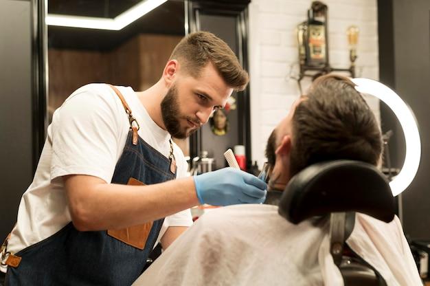 Jonge man die zijn baard laat stylen bij de kapper