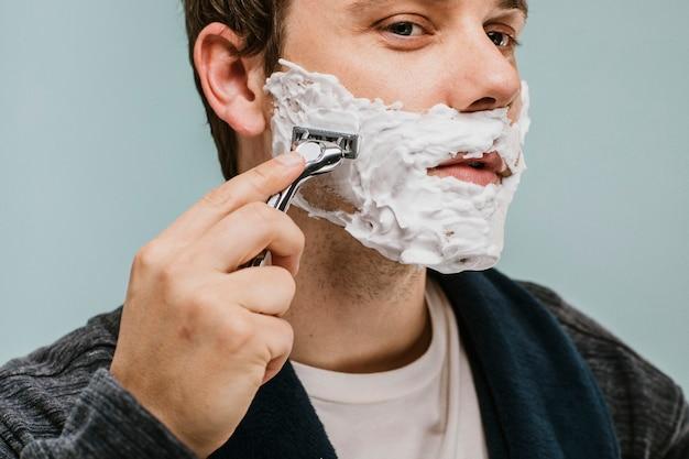 Jonge man die zijn baard scheert