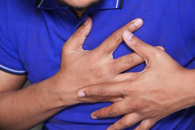 Jonge man die zijn borst met zijn handen houdt